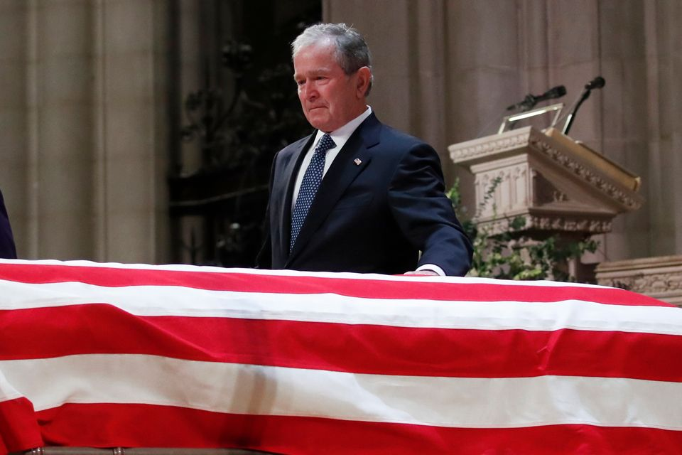 Former President George W. Bush touches the casket of his father, former President George H.W. Bush, at the State Funeral at