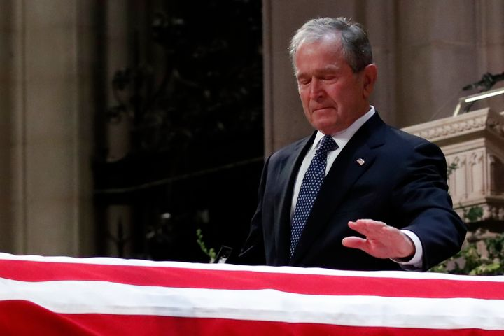 "Bush touches his father's casket during the funeral ceremony. He praised him as ""the best father a son or daughter could"