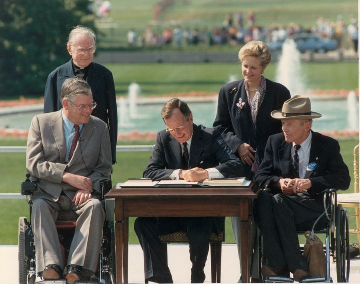 In this file photo from 1990, George H.W. Bush signs the Americans With Disabilities Act. The former president died last week