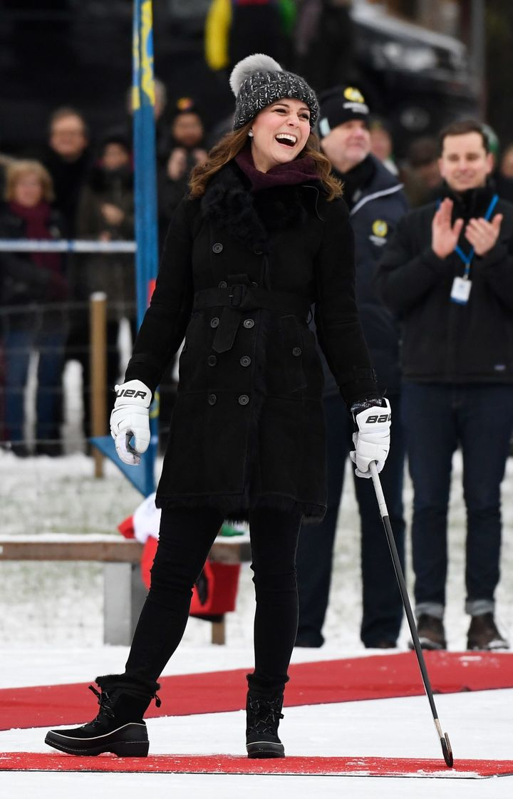The Duchess of Cambridge laughs as she tries out the game of bandy during a meeting with a group of local bandy players on th