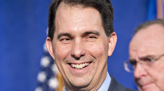Scott Walker, governor of Wisconsin, smiles after signing an Electronics and Information Technology Manufacturing Zone Tax Credit Agreement during an event in Racine, Wisconsin, U.S., on Friday, Nov. 10, 2017. The agreement grants Foxconn $3 billion in tax incentives for a massive manufacturing campus in southeastern Wisconsin. Photographer: Daniel Acker/Bloomberg via Getty Images