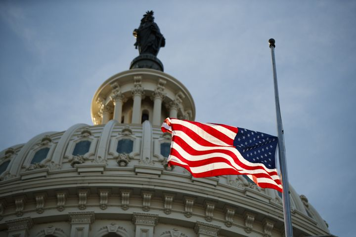 An American flag flies at half-staff at the U.S. Capitol in Washington on Monday, following the death of former President George H.W. Bush.