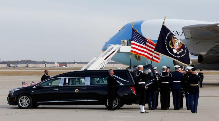 The flag-draped casket of former President George H.W. Bush is carried by a joint services military honor guard during a depa