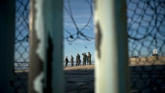 U.S. Border Patrol agents stand near the wall at the playas of Tijuana, Mexico, Sunday, Dec. 2, 2018. Thousands of migrants who traveled via caravan are seeking asylum in the U.S., but face a decision between waiting months or crossing illegally, because the U.S. government only processes a limited number of cases a day at the San Ysidro border crossing in San Diego. (AP Photo/Ramon Espinosa)
