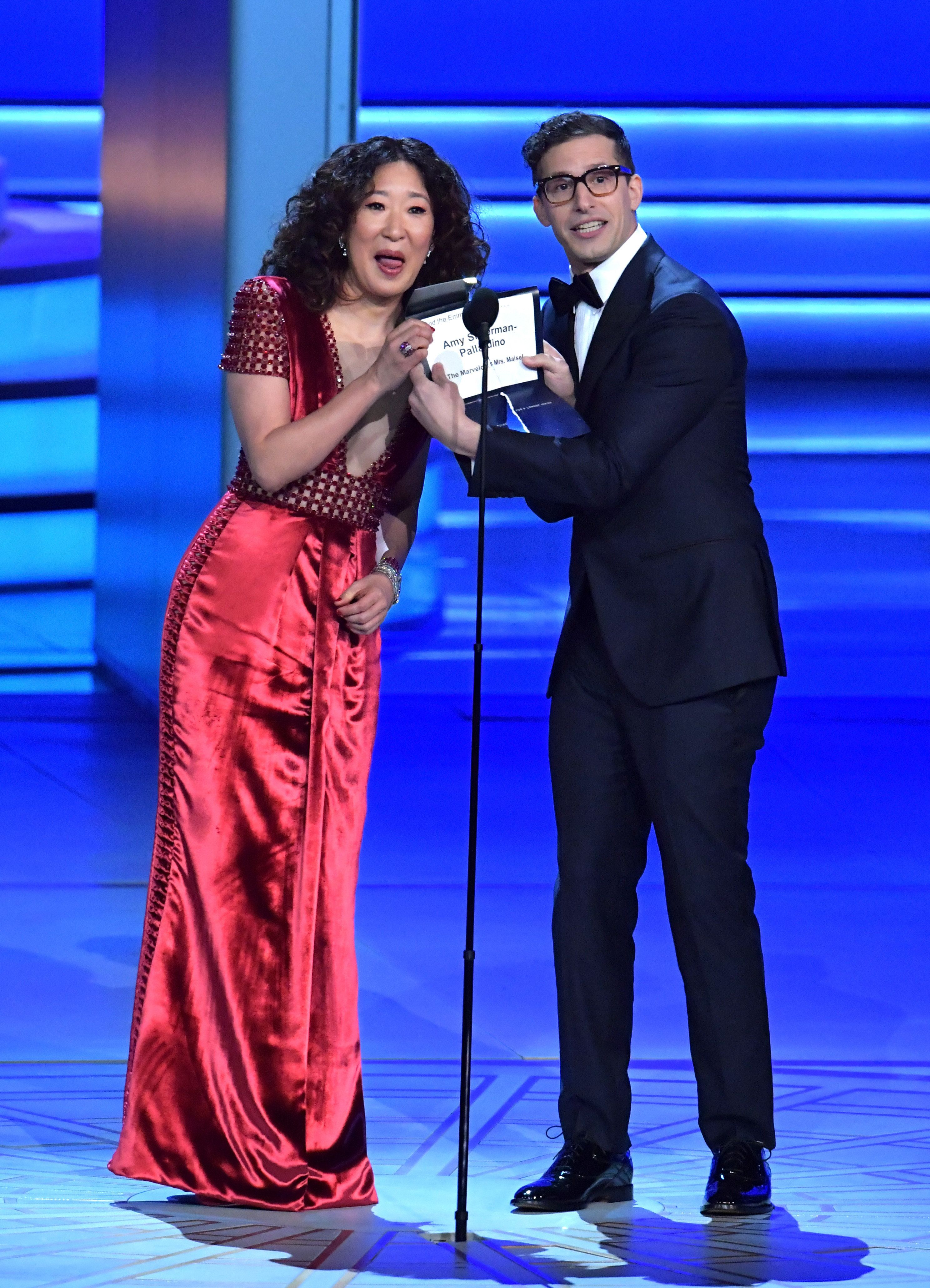 LOS ANGELES, CA - SEPTEMBER 17:  Sandra Oh (L) and Andy Samberg speak onstage during the 70th Emmy Awards at Microsoft Theater on September 17, 2018 in Los Angeles, California.  (Photo by Lester Cohen/WireImage)