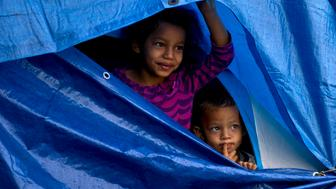 Migrants, who are part of the central American migrant caravan, take refuge from the rain in a makeshift tent at a sports complex where more than 5,000 Central American migrants are sheltering in Tijuana, Mexico, Thursday, Nov. 29, 2018. As Mexico wrestles with what to do with the thousands of people camped out in the border city of Tijuana, President-elect Andres Manuel Lopez Obrador's government signaled that it would be willing to house the migrants on Mexican soil while they apply for asylum in the United States, a key demand of U.S. President Donald Trump. (AP Photo/Ramon Espinosa)