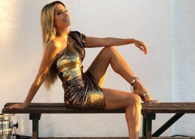 Sylvie Meis in einem goldenen asymmetrischem Kleid und High-Heels.