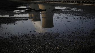 Cooling towers are reflected in a puddle at the American Electric Power Co. Inc. coal-fired John E. Amos Power Plant in Winfield, West Virginia, U.S.