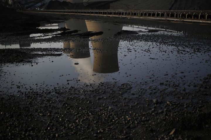 Cooling towers are reflected in a puddle at the American Electric Power Company's coal-fired John E. Amos Power Plant in Winf