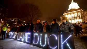 "Opponents of an extraordinary session bill submitted by Wisconsin Republican legislators hold ""Stop Lame Duck"" signs at a rally outside the Wisconsin state Capitol in Madison, Wis., Monday, Dec. 3, 2018. (John Hart/Wisconsin State Journal via AP)"