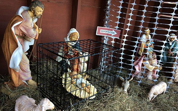 In St. Susanna Parish's Nativity display, Jesus is placed in a metal cage while the wise men are blocked by a fence.