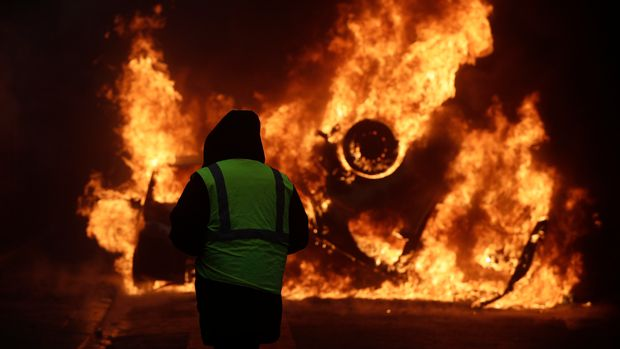 A demonstrator watches a burning car near the Champs-Elysees avenue during a demonstration Saturday, Dec.1, 2018 in Paris. French authorities have deployed thousands of police on Paris' Champs-Elysees avenue to try to contain protests by people angry over rising taxes and Emmanuel Macron's presidency. (AP Photo/Kamil Zihnioglu)