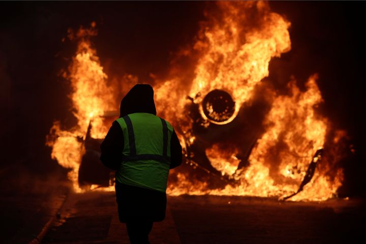 A demonstrator watches a burning car near the Champs-Elysees avenue during a demonstration last Saturday in Paris.