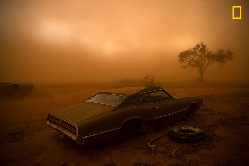 A rusting Ford Thunderbird is blanketed by red dust from a supercell thunderstorm in Ralls, Texas. The dry, plowed fields of