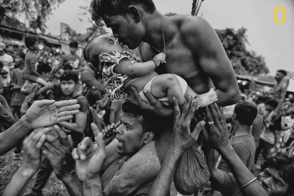 A Hindu devotee kisses his newborn baby during the Charak Puja festival in West Bengal, India. Traditional practice calls for the devotee to be pierced with a hook and sometimes swung from a rope. This painful sacrifice is enacted to save their children from anxiety. While covering the festival, I was able to view the religious practice from the perspective of Hindu devotees. I tried to capture the moment of love and bonding between a father and his child -- and show a father's concern for his little son.
