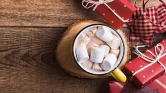 Mug of hot chocolate with marshmallows and Christmas gift boxes on wooden  background viewed from above