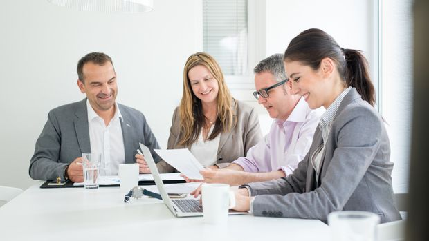 Business team in discussion around a table in a modern startup office.