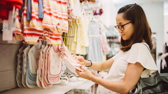 Young pregnant mom shopping for baby clothes joyfully in the department store
