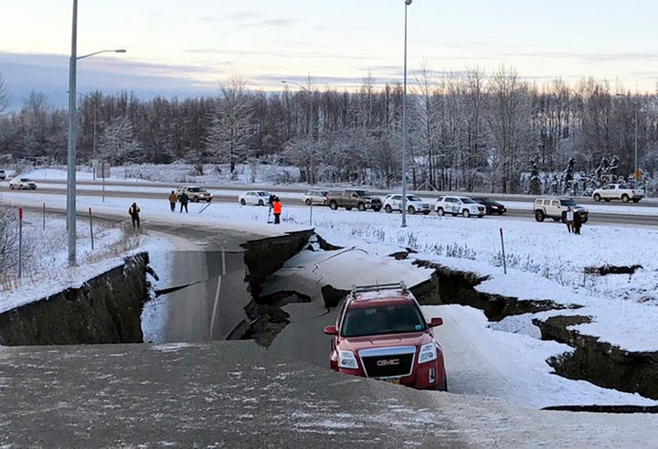 A vehicle is trapped on a section of road that collapsed during an earthquake in Anchorage, Alaska.
