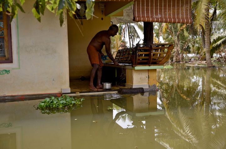 A man stands in his house amid flood waters in Kerala, India — the worst monsoon flooding in a century in the southern