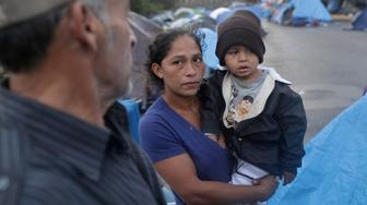 TIJUANA, MEXICO - DECEMBER 06:  Honduran migrant Jenny Cantarero holds her son Saul, 3, where they are living outside a closed temporary migrant shelter near the U.S.-Mexico border fence on December 6, 2018 in Tijuana, Mexico. After traveling more than six weeks from Central America and arriving to the U.S. border, members of the migrant caravan are increasingly seeing the long odds of crossing successfully into the United States.  (Photo by John Moore/Getty Images)