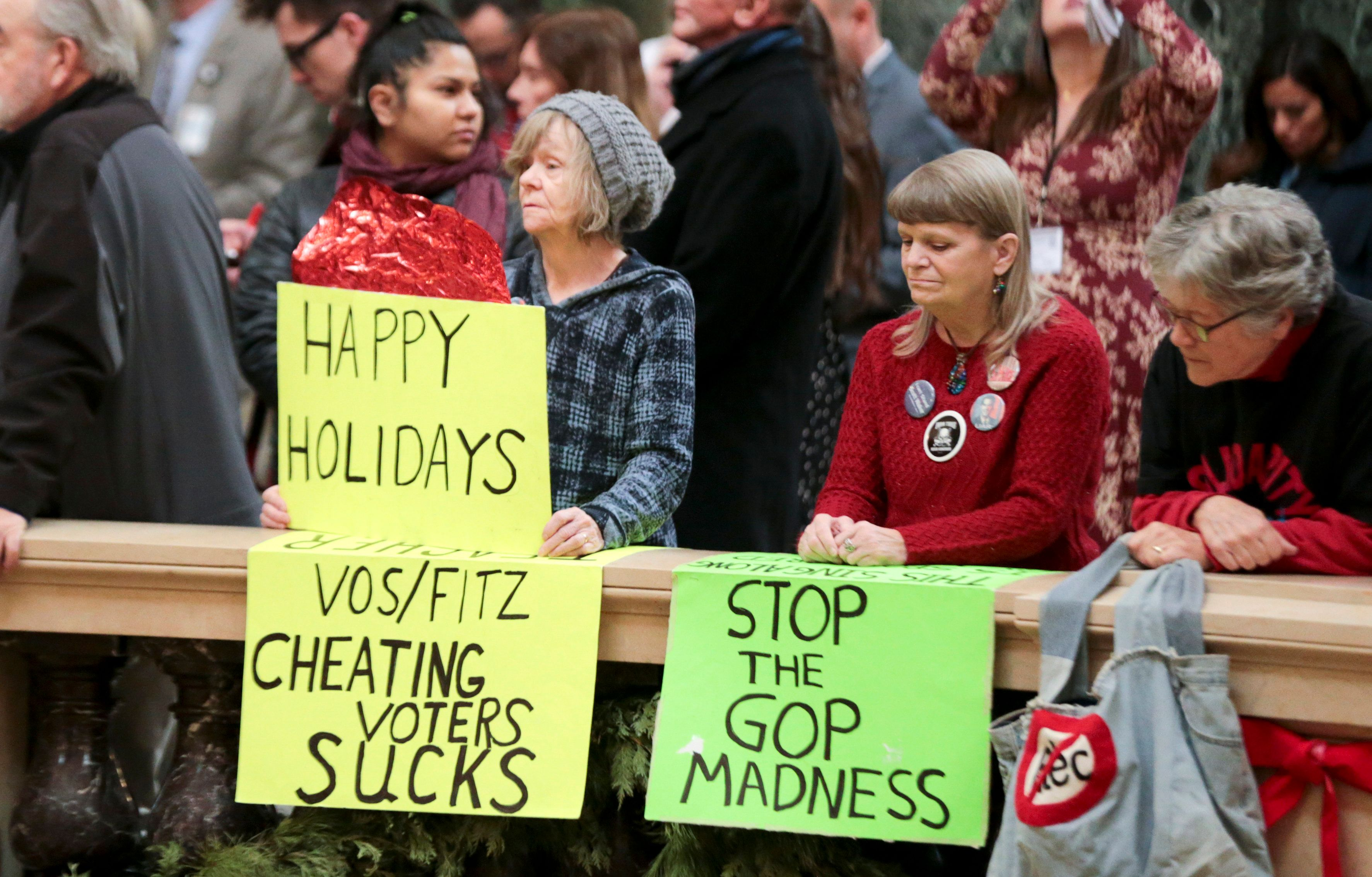 Protesters Peppi Elder, left, and Christine Taylor holds up signs during the state Christmas Tree lighting ceremony in state Capitol Rotunda Tuesday Dec. 4, 2018, in Madison, Wis. The Senate and Assembly are set to send dozens of changes in state law to Gov. Scott Walker's desk. (Steve Apps