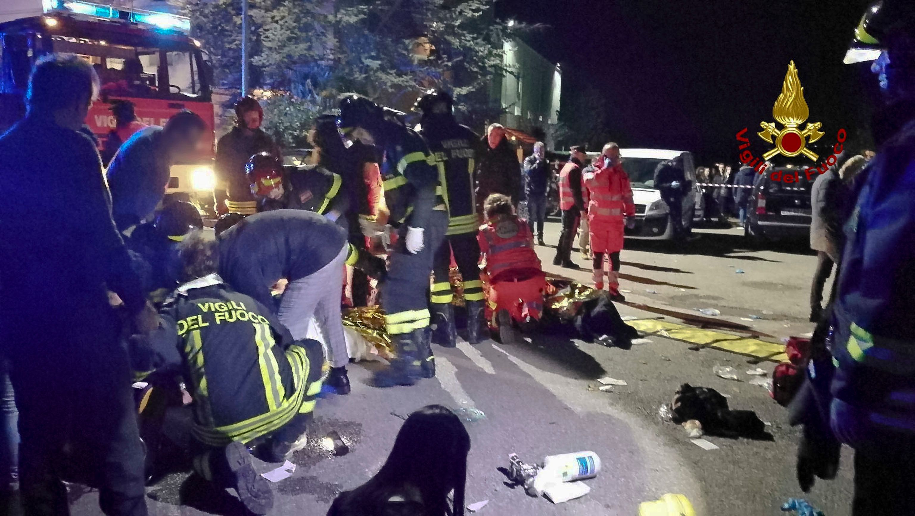 In this frame taken from video rescuers assist injured people outside a nightclub in Corinaldo, central Italy, early Saturday, Dec. 8, 2018. At least Six people, all but one of them minors, were killed and about 35 others injured in a stampede of panicked concertgoers early Saturday at a disco in a small town on Italy's central Adriatic coast. (Vigili del Fuoco via AP)