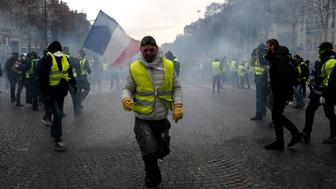 A demonstrator wearing a yellow vest grimaces through tear gas Saturday, Dec. 8, 2018 in Paris. Crowds of yellow-vested protesters angry at President Emmanuel Macron and France's high taxes tried to march Saturday on the presidential palace, surrounded by exceptional numbers of police bracing for outbreaks of violence after the worst rioting in Paris in decades. (AP Photo/Rafael Yaghobzadeh)
