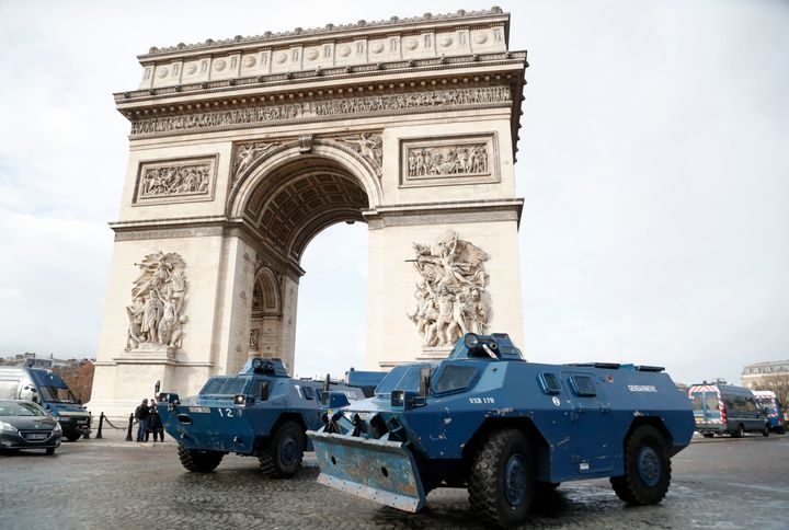 Police armoured personnel carriers are parked in front of the Arc de Triomphe.