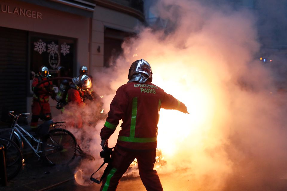 Emergency workers attempt to quash flash fires across Paris on Saturday after riots flared once
