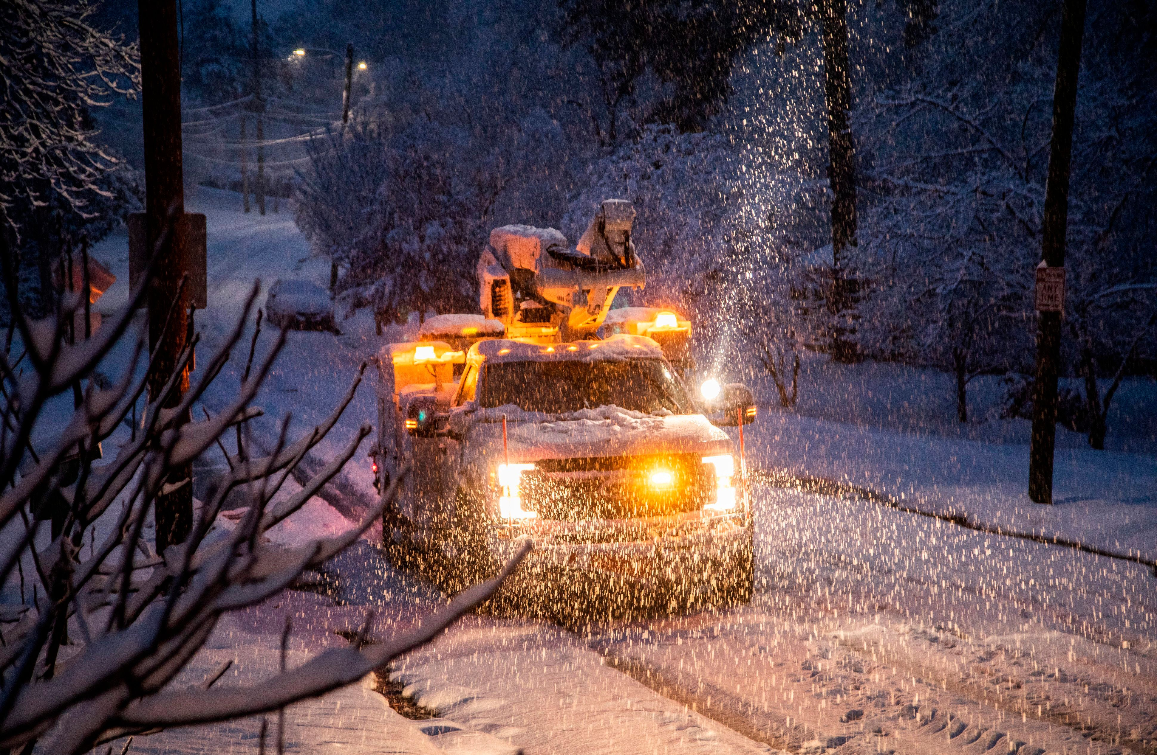 A Duke Energy crew works to restore power in Raleigh, N.C,. as snow continues to fall Sunday morning, Dec. 9, 2018. A storm spreading snow, sleet and freezing rain across a wide swath of the South has millions of people in its path, raising the threat of immobilizing snowfalls, icy roads and power outages. (Travis Long/The News & Observer via AP)