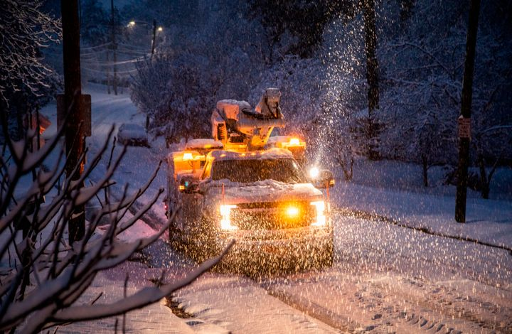 A Duke Energy crew works to restore power in Raleigh, N.C,. as snow continues to fall Sunday morning, Dec. 9, 2018.
