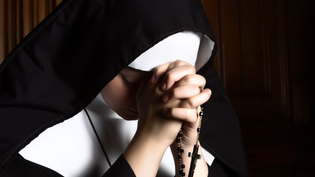 Fine art portrait of a novice nun in deep prayer with rosary