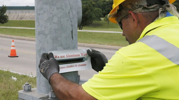 David Tubb puts a sticker on the base of a streetlight in Tulsa, Oklahoma, where new aluminum wiring was installed last year.