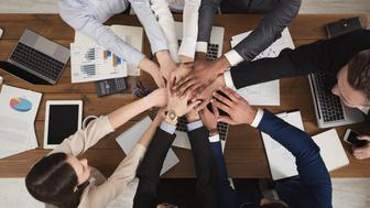 United coworkers standing with their hands together above workplace in modern office, celebrating successful project, top view, teambuilding and unity background