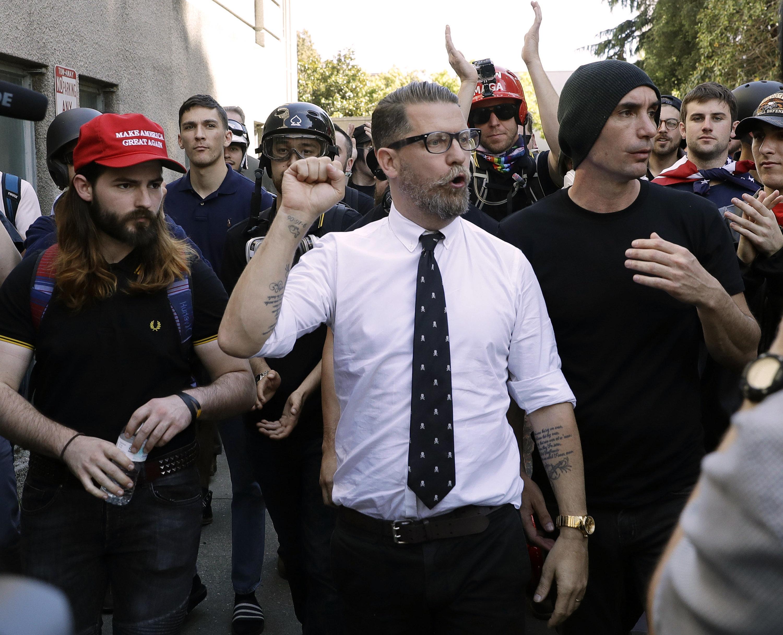 ARCHIVO - En esta fotografía de archivo del 27 de abril de 2017, Gavin McInnes, centro, cofundador del grupo de la extrema derecha Proud Boys, está rodeado de sus partidarios en un evento en Berkeley, California. (AP Foto/Marcio Jose Sanchez, Archivo)