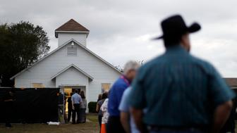 A group wait in line to enter the Sutherland Springs Baptist Church to view a memorial, Sunday, Nov. 12, 2017, in Sutherland Springs, Texas. A man opened fire inside the church in the small South Texas community last week, killing more than two dozen. The sanctuary has been converted to a memorial to honor the victims. (AP Photo/Eric Gay)