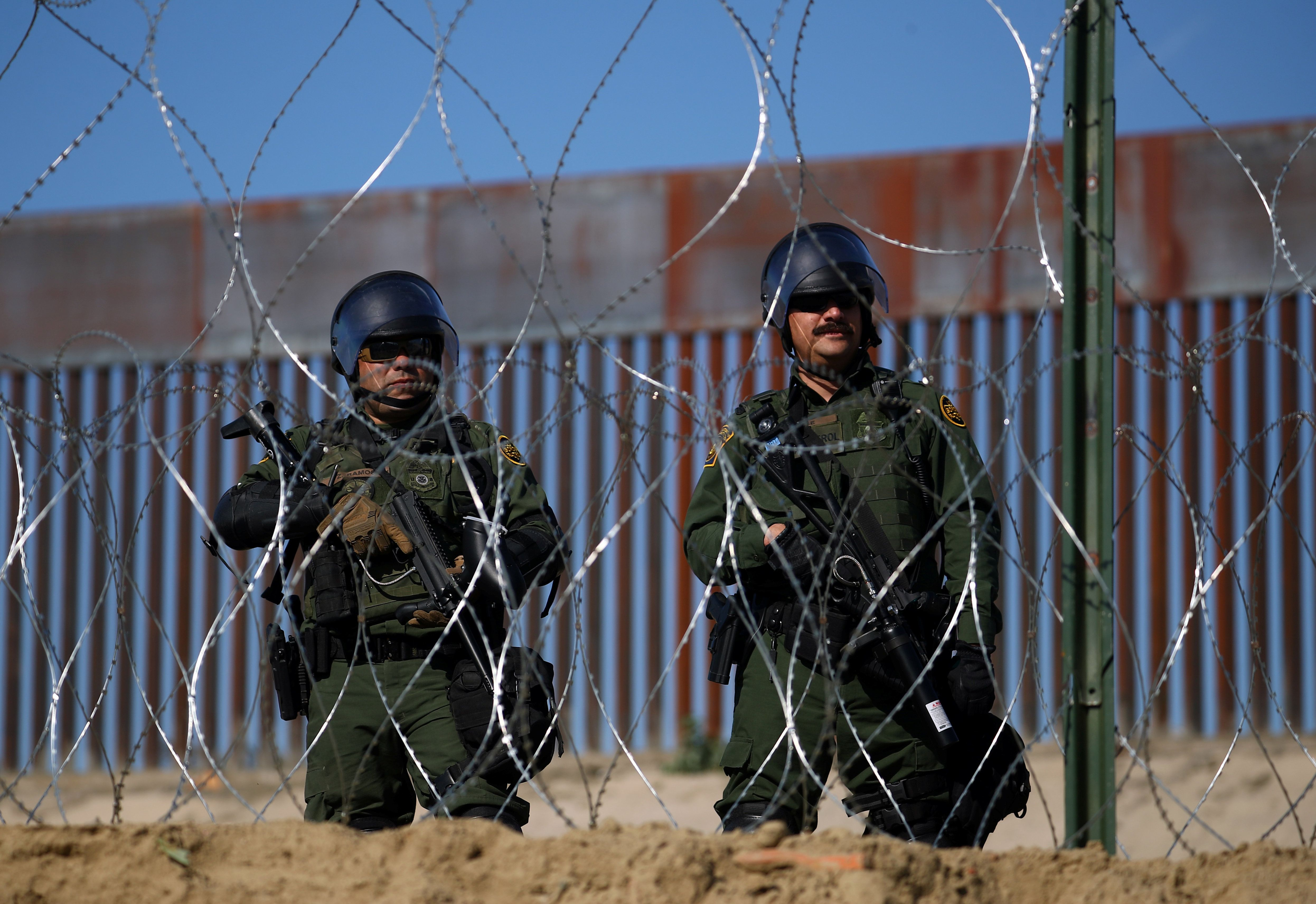Members of a U.S. border patrol stand near the border fence between Mexico and the United States as migrants stand near by in Tijuana, Mexico, November 25, 2018. REUTERS/Hannah McKay