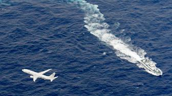 FILE - In this Dec. 6, 2018, file photo, Japan's Coast Guard ship, top, and U.S. military plane are seen at sea off Kochi, southwestern Japan, during a search and rescue operation for missing crew members of a U.S. Marine refueling plane and fighter jet. The U.S. Marine Corps have declared that five crewmembers dead after their aircraft crashed last week off Japan's southern coast and that their search has ended. (Kyodo News via AP, File)