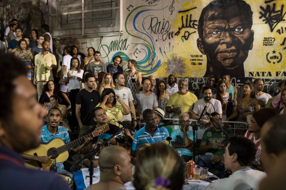 In this March 29, 2016 photo, people listen to live samba music at Pedra do Sal in Rio de Janeiro. A mural in the background