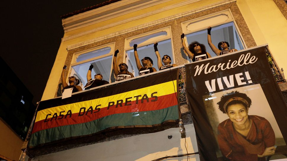 Demonstrators gesture as they protest the shooting of Rio de Janeiro city council member Marielle Franco, in front of the Cas