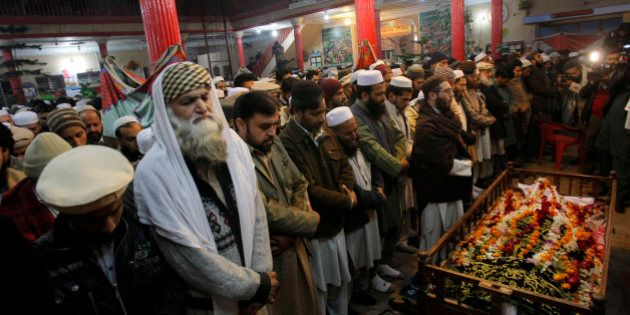Mourners and relatives of Pakistani teacher, Saeed Khan, a victim of a Taliban attack in a school, pray...