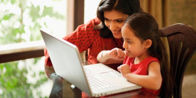 mother and daughter working at laptop