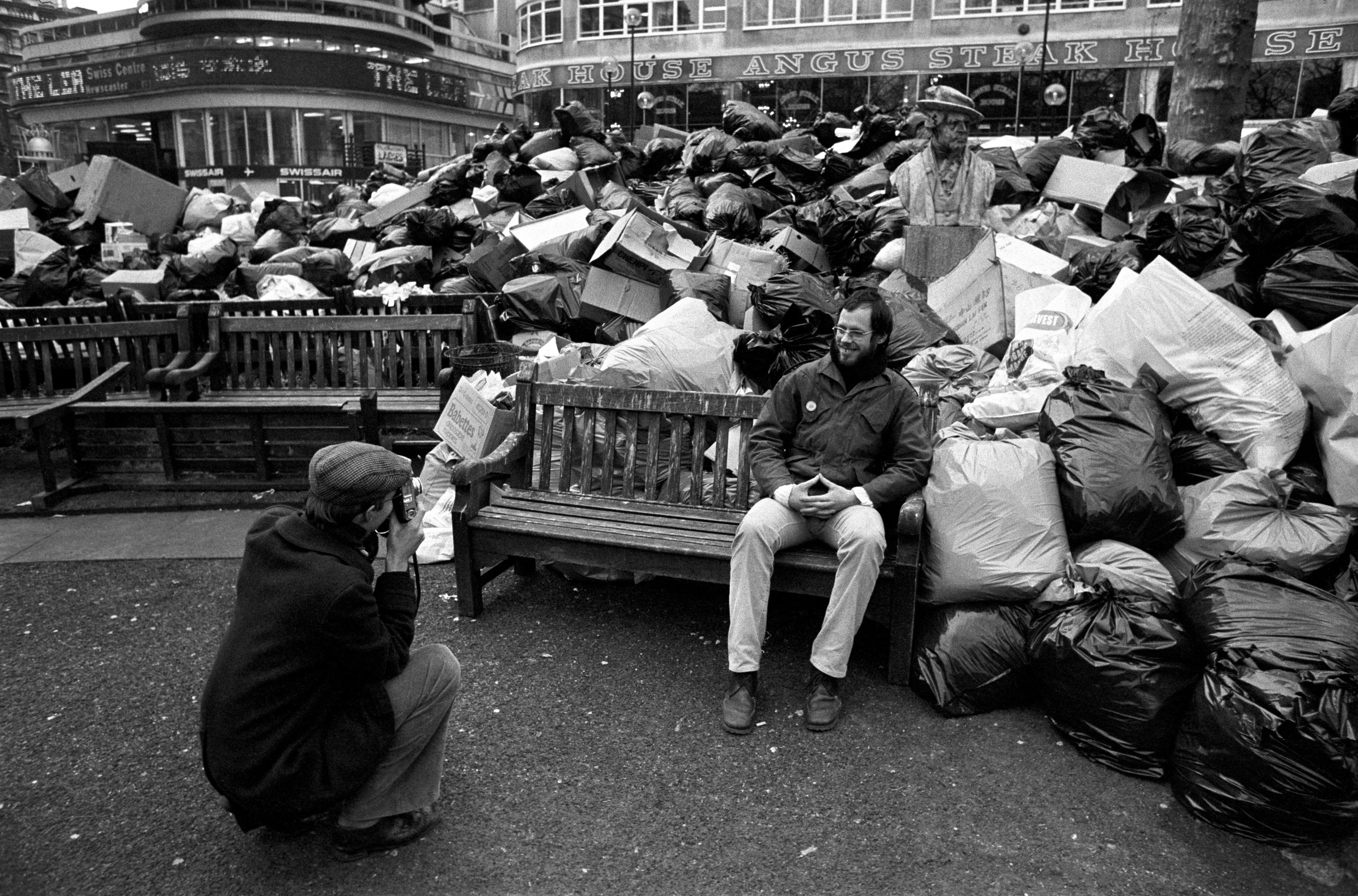 Two Dutch tourists take a photograph in London's Leicester square, where rubbish piled up during the...