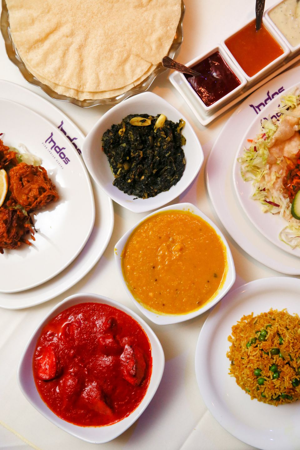 A selection of Indian food sits on a table in the Indo Indian fine dining restaurant in Chobham, U.K., on Wednesday, Nov. 14, 2018. Almost two decades after chicken tikka masala was unofficially declared Britain's national dish, pro-Leave politicians promised restaurants higher inflows from South Asia with easier visa rules, shutting the door on European workers, allowing lower salary-thresholds to hire overseas staff and even regularizing undocumented workers. Photographer: Luke MacGregor/Bloomberg via Getty Images