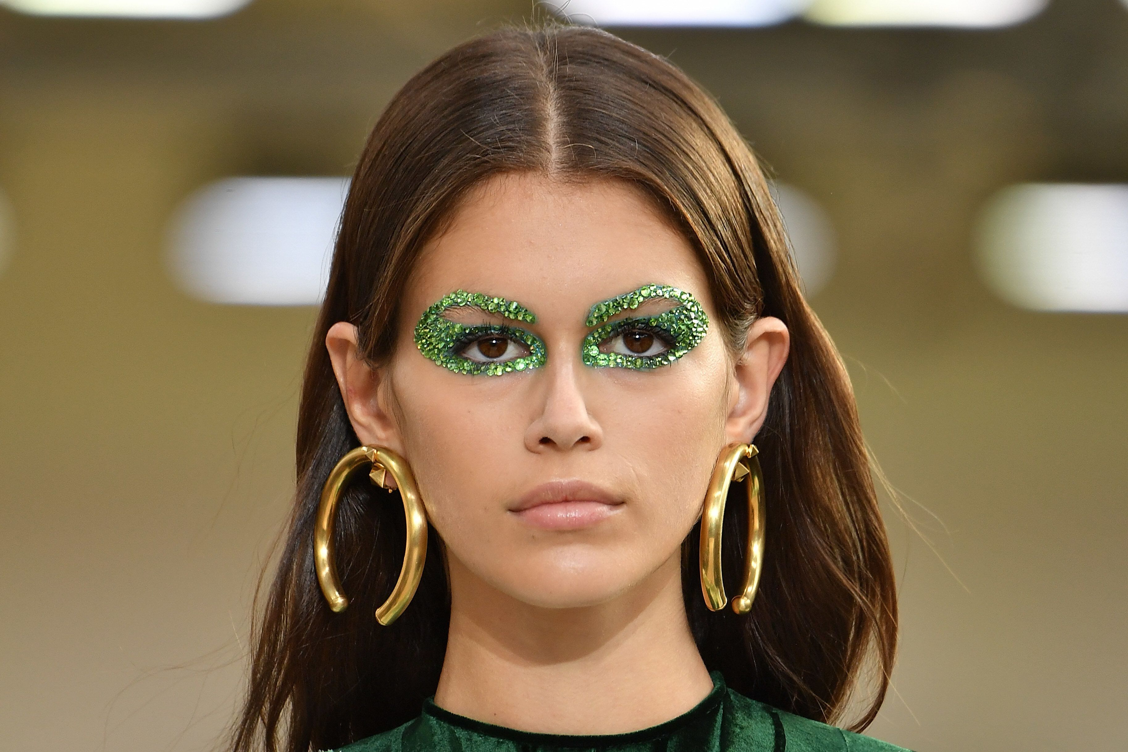 Kaia Gerber walking the runway with some very glittery eye makeup at the Valentino spring 2019 show in Paris.