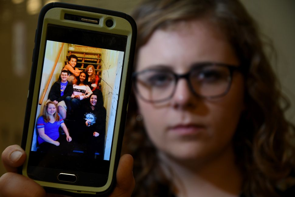 Price shows her phone screensaver, which features a photo of her and some friends, including