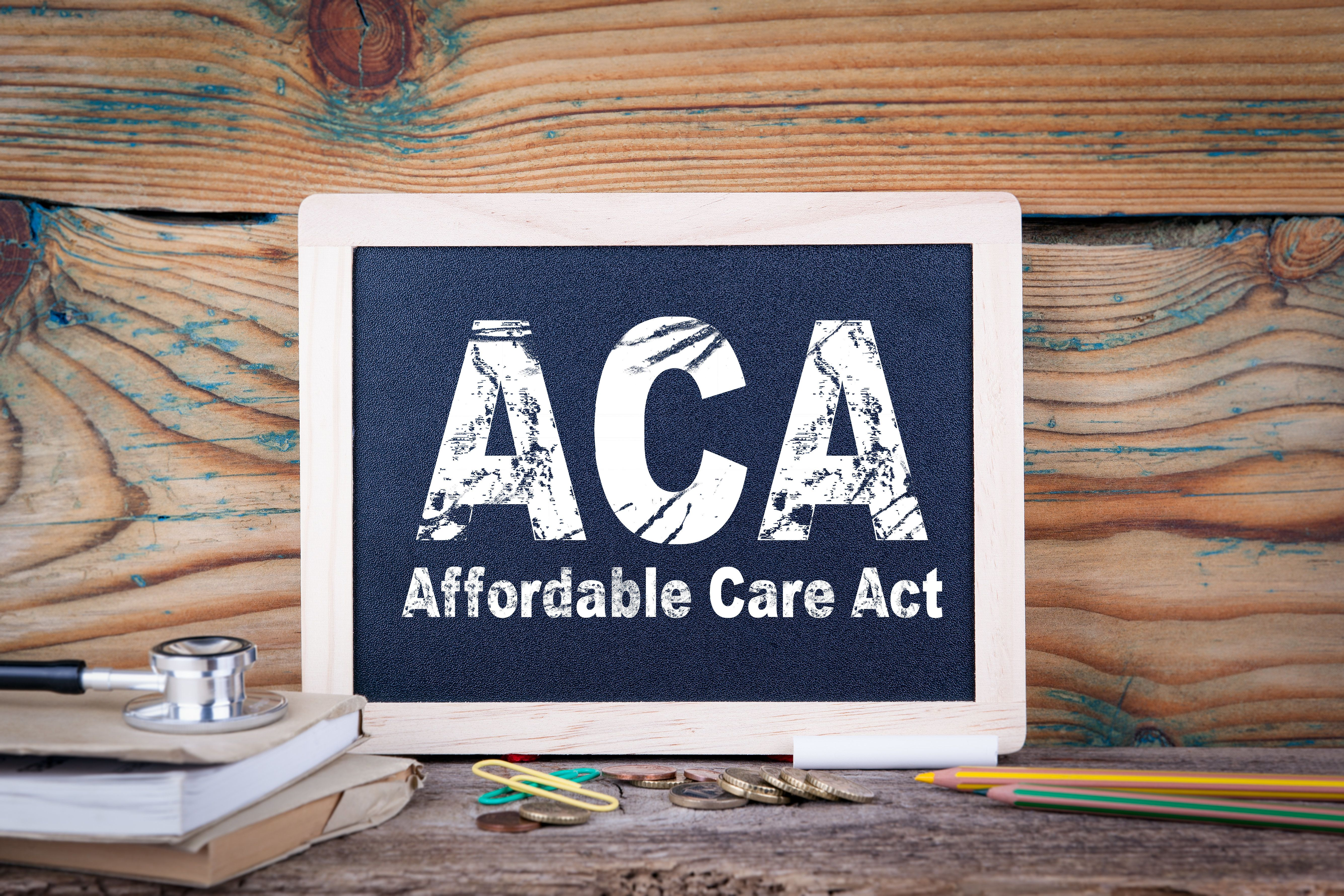 aca, affordable care act. Chalkboard on a wooden background