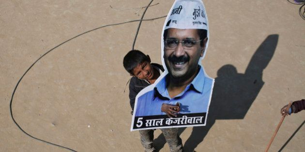 A boy looks on as he holds a portrait of Arvind Kejriwal, chief of Aam Aadmi (Common Man) Party (AAP)...