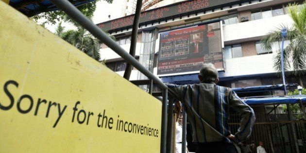 MUMBAI, INDIA - JUNE 25: People look at a screen across a road displaying the Sensex on the facade of...